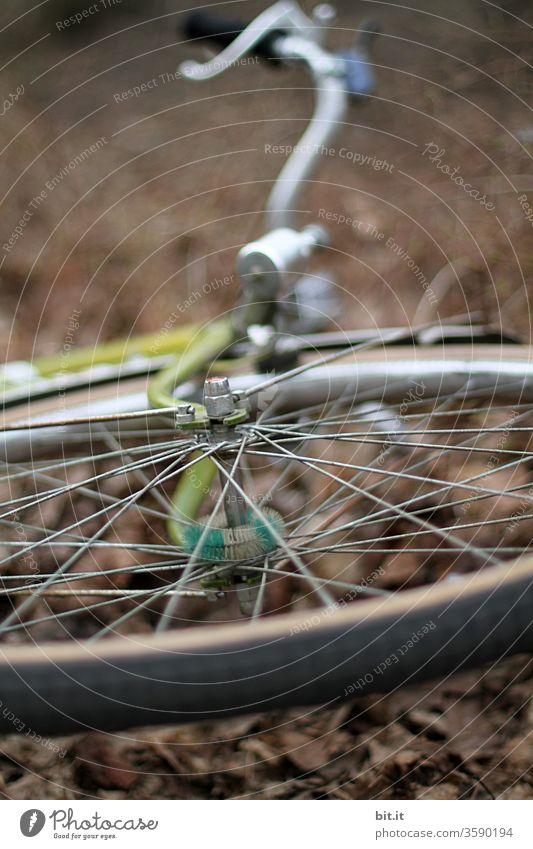 Vorderreifen, Radnarbe, Lenker, Dynamo vom Fahrrad von unten mit schwacher Tiefenschärfe. Gestohlenes, geklautes Rad liegt liegen gelassen auf dem braunen herbstlichen Boden. Umgefallenes Rad, nach Unfall, Sturz, Umkippen auf der Seite liegend im Herbst.