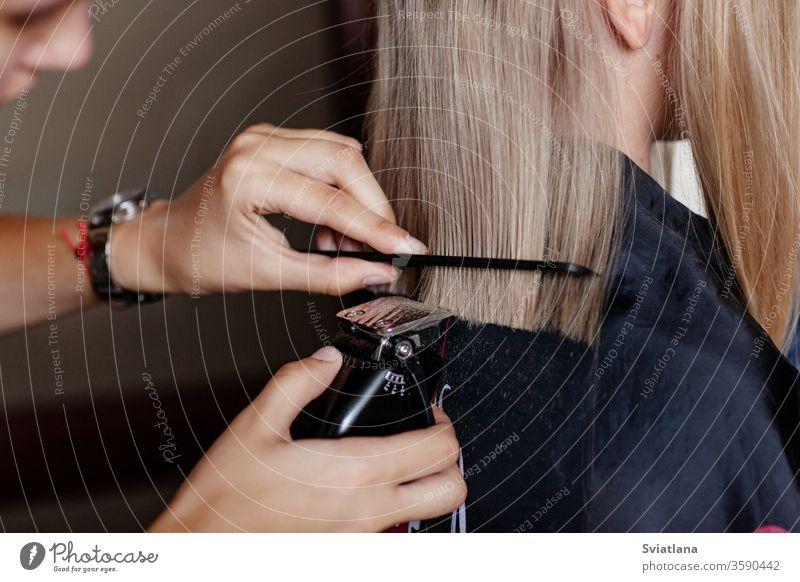 Der Friseur macht einen modischen Haarschnitt für ein Mädchen mit einem Haarschnitt. Behaarung Salon Maschine Hand professionell Mode Stil geschnitten Klient