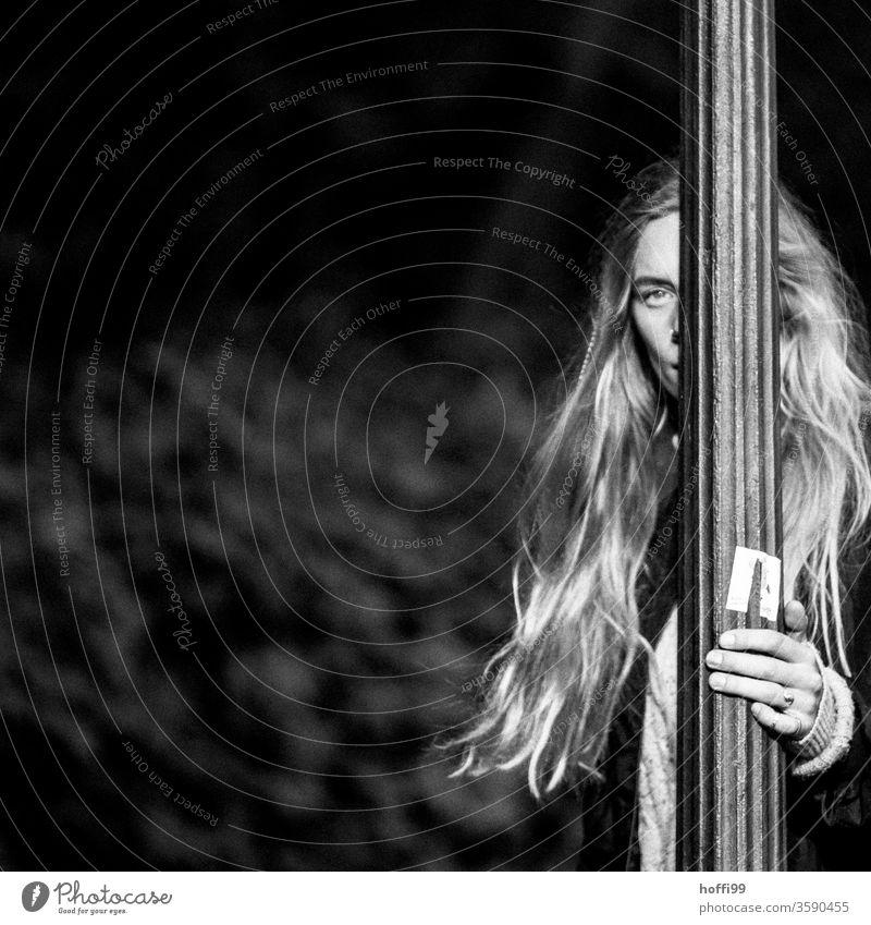 die junge Frau, halb versteckt hinter dem Laternenfahl, blickt in die Kamera Junge Frau Frauengesicht unscharfer Hintergrund 18-30 Jahre Erwachsene Haarsträhne