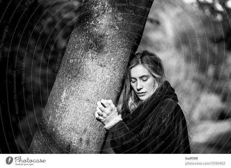 die junge Frau lehnt sich an einen Baum und schaut nachdenklich herunter Junge Frau blond Melancholie langhaarig blondes Haar langes Haar Haare & Frisuren Kopf