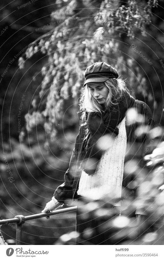 die junge Frau schlendert nachdenklich und in sich ruhend durch den Park Junge Frau Melancholie Frauengesicht unscharfer Hintergrund 18-30 Jahre Erwachsene