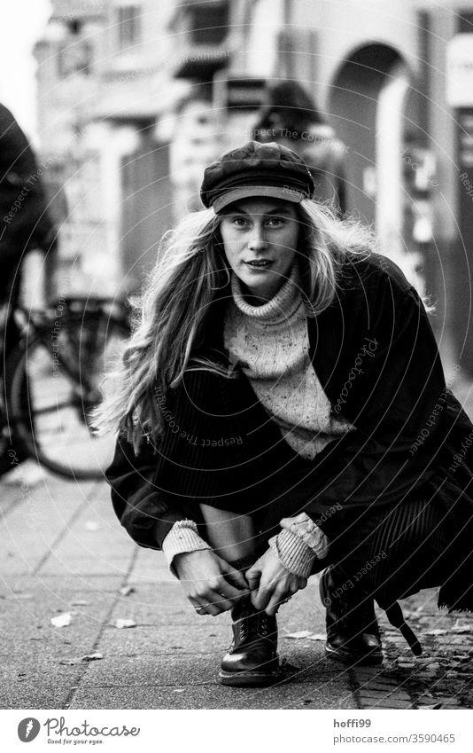 die junge Frau bindet sich die Schuhe zu und blickt in die Kamera feminin Junge Frau Kopf 18-30 Jahre Frauengesicht natürlich Gesicht portraite Jugendliche