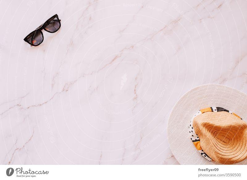 Flache Anordnung von Objekten aus den Bereichen Sommer, Frühling und Freizeit vor einem Marmorhintergrund Sonnenbrille Hut flache Verlegung Flachlegung
