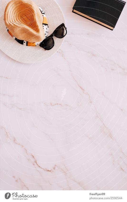 Flache Anordnung von Objekten aus den Bereichen Sommer, Frühling und Freizeit vor einem Marmorhintergrund Sonnenbrille Hut Buch lesen flache Verlegung