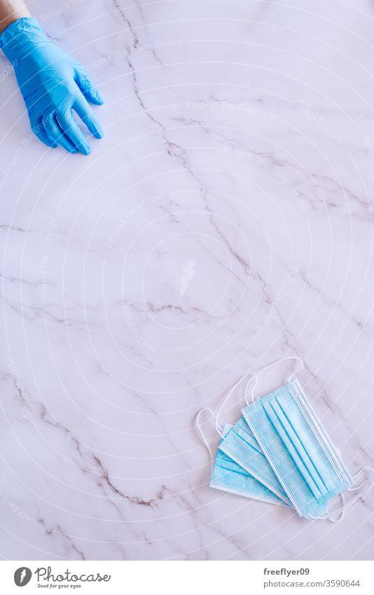 Flacher Handaufschlag auf medizinische Handschuhe und einige chirurgische Masken vor einem Marmorhintergrund Mundschutz Gesundheit Atem Kinderzimmer Medizin