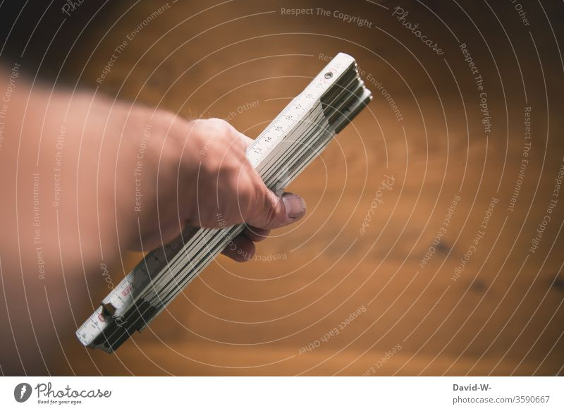 Handwerk - Mann hält einen Zollstock in der Hand Handwerker heimwerken bauen planen messen ausmessen nachmessen Holzboden Parkettboden Perspektive kreativ