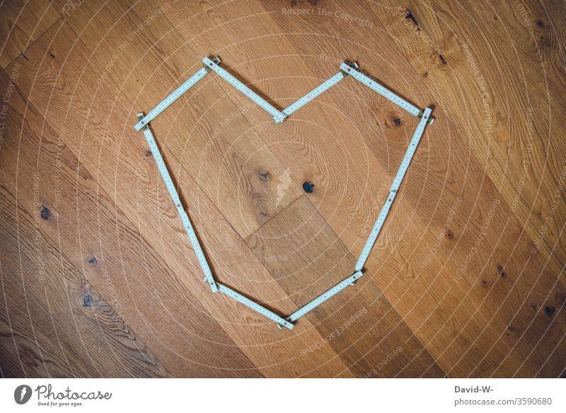 Handwerker aus Leidenschaft Zollstock heimwerken bauen planen messen ausmessen nachmessen Holzboden Parkettboden Perspektive kreativ Baustelle Farbfoto Werkzeug