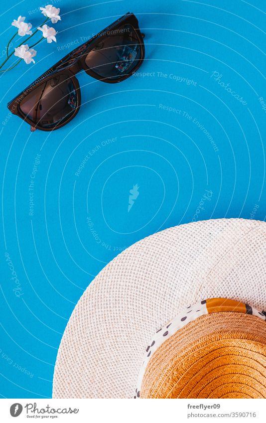 Flächige Darstellung von Objekten im Zusammenhang mit Sommer und Frühling vor blauem Hintergrund Sonnenbrille Hut flache Verlegung Flachlegung Textfreiraum