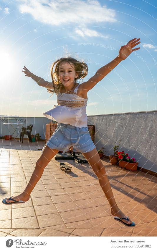Hübsches kleines Mädchen in weißem Tanktop, das bei Sonnenuntergang auf der Terrasse des Hauses tanzt und springt Natur Fröhlichkeit Himmel schön Spielen