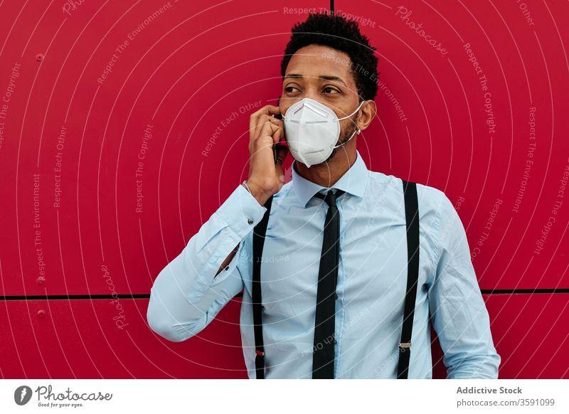 Seriöser ethnischer Geschäftsmann mit Atemschutzgerät spricht mit Smartphone auf der Straße Telefonanruf Mundschutz behüten Großstadt reden Pandemie Infektion