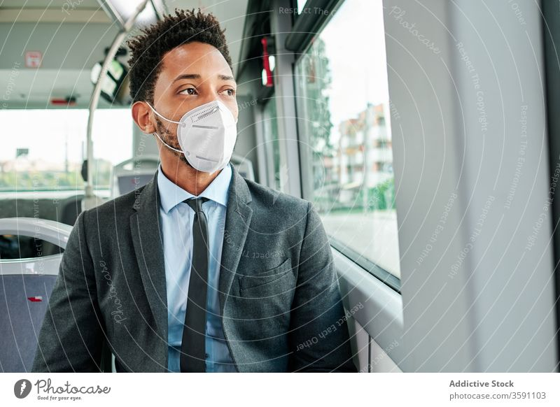 Schwerer männlicher Unternehmer trägt Atemschutzgerät im Bus Mann Öffentlich Verkehr Mundschutz behüten Coronavirus Ausbruch Passagier ethnisch schwarz