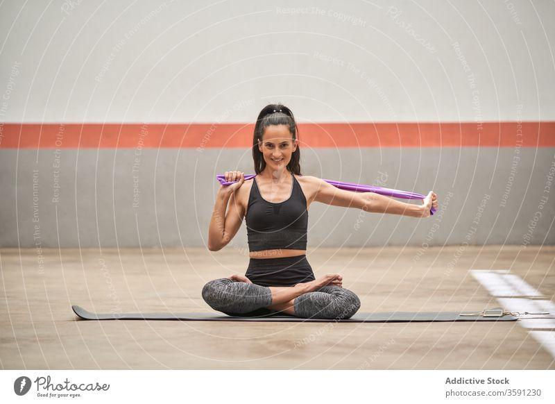 Lächelnde Frau in Lotus-Pose im Fitnessstudio Yoga meditieren ruhig Unterlage padmasana Sportbekleidung Gesundheit Wellness Windstille widersetzen elastisch