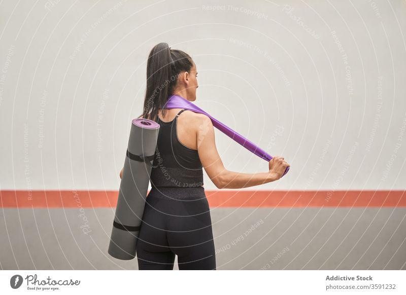Sportlerin mit Gummiband und Matte nach dem Training Fitnessstudio Unterlage Band elastisch widersetzen Sportbekleidung schlank Frau Leggings BH Inhalt