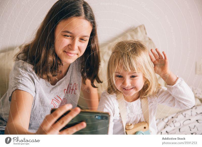Fröhliche Schwestern, die sich zu Hause am Smartphone vergnügen Selfie Grimasse Mädchen Geschwisterkind benutzend Spaß haben gestikulieren Teenager wenig