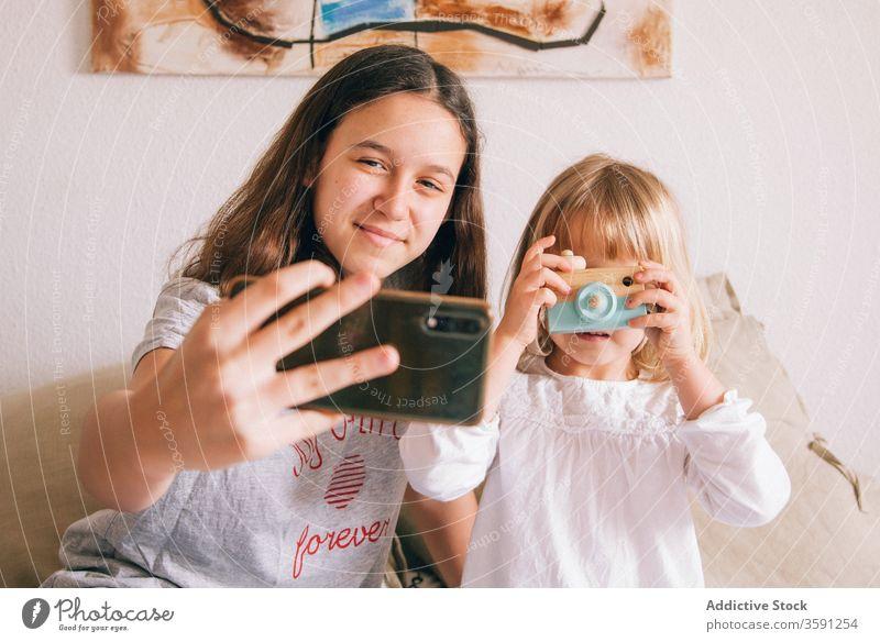 Zufriedene Schwestern nehmen Selbstliebe am Mobiltelefon Selfie Smartphone Teenager wenig Mädchen benutzend charmant Inhalt Spaß haben Spielzeug Fotokamera