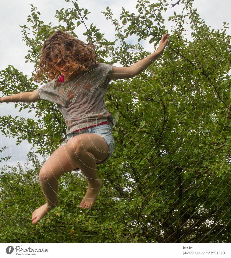 Lockiger, temperamentvoller Spaßvogel springt auf Trampolin im Garten. Mädchen fliegt, hüpft, springt lebensfroh, glücklich, wild, verrückt nach oben. Sport, Unbeschwertheit, Bewegung und Fitness gegen Stress, Probleme, Angst in der Schule und zu Hause.