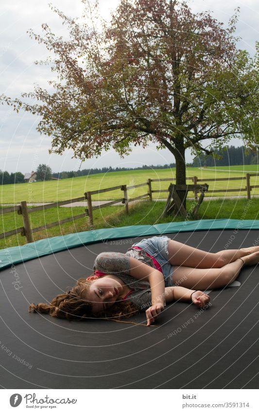 Müder, weiblicher Teenager liegt faul auf Trampolin im Garten und betrachtet seine lockigen Haare. Langhaarige, brünette Jugendliche chillt auf Trampolin in der Natur und sucht Haarspliss in Haarsträhne. Pause, Ausruhen, Entspannen, Erholen nach Sport.