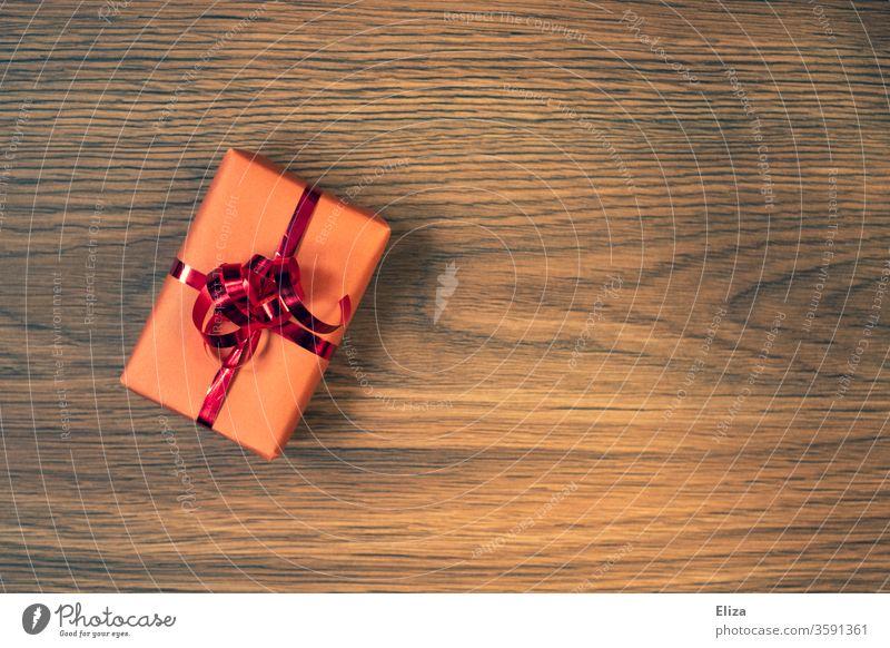 Ein verpacktes Geschenk mit rotem Geschenkband auf Untergrund aus Holz Verpackung Geburtstag Weihnachten Weihnachtsgeschenk Geburtstagsgeschenk rosa Vorfreude