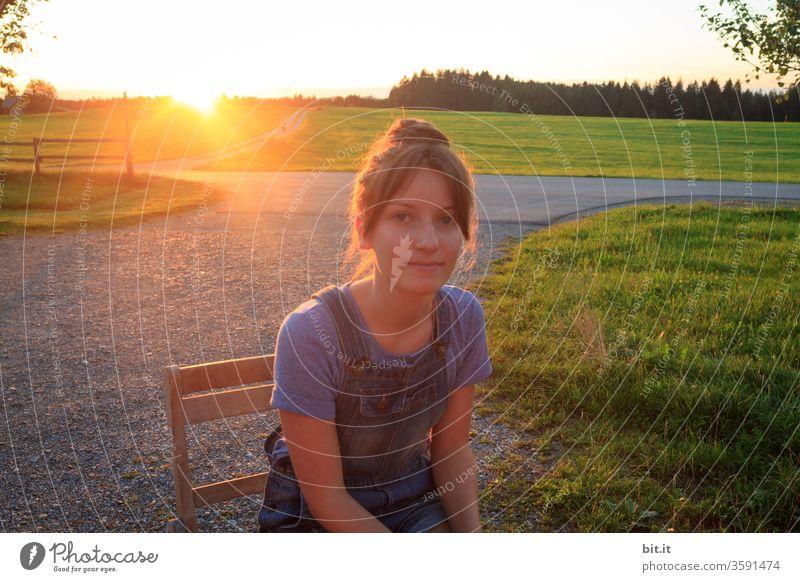 Teenager sitzt bei Sonnenuntergang auf einem Weg mit Kieselsteinen, auf einem Holzstuhl und schaut in die Kamera. Jugendliche genießt sitzend die Abendsonne, im Sommerurlaub auf dem Land, vor grüner Landschaft, Wiesen, Weide, Wald und warmen Sonnenlicht.