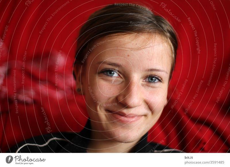 Fröhlicher, optimistischer, hübscher Teenager lächelt freundlich, verschmitzt, vor rotem Hintergrund in die Kamera. Lebenslustige, lebensfreudige, glückliche Jugendliche mit blauen Augen, strahlendem Blick, post vor rotem, leuchtendem Vorhang, im Theater.