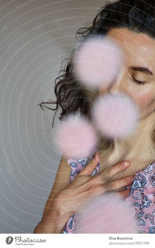 Frau mit geschlossenen Augen, Blumen verdecken ihren Mund und ein Auge Studioaufnahme Farbfoto Scham Gefühle schwarz 30-45 Jahre Erwachsene feminin Mensch