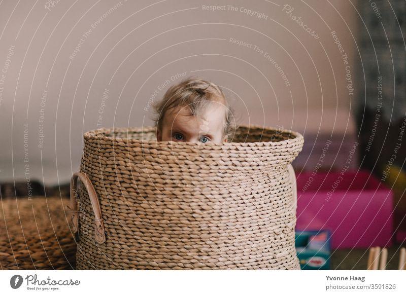 Babyaugen schauen aus einem Korb heraus lachendes kind kleines kind kleiner Junge kleines Mädchen strahlend versteckend Erholung Kindererziehung
