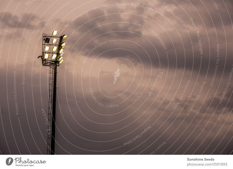 Helle Lichter im Sportstadion an einem bewölkten Abend Stadion Sportplatz Flutlicht Silhouette leuchten wolkig Glanz Glühbirne hell Unwetter stürmisch