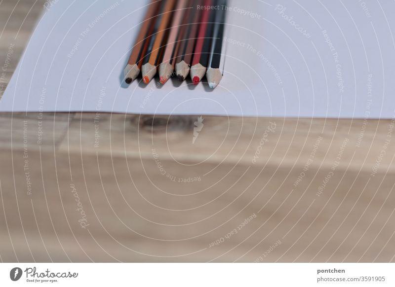 Buntstifte für verschiedene Hautfarben liegen auf einem weißen Blatt   Papier. Diversität, Vielfalt  , offen,  antirassismus, bunt. Weiß, schwarz, rosa, braun, orange, rot