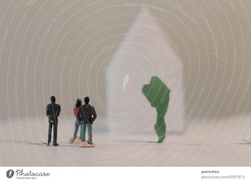Living in a white world. Zwei männliche und  eine weibliche Modellfigur  stehen vor einem weißen Haus und weißem Hintergrund  aus Papier. Symbolik . Dominanz der weißen  Menschen. Rassismus , Ignoranz. Bastelarbeit . Architektur, makler