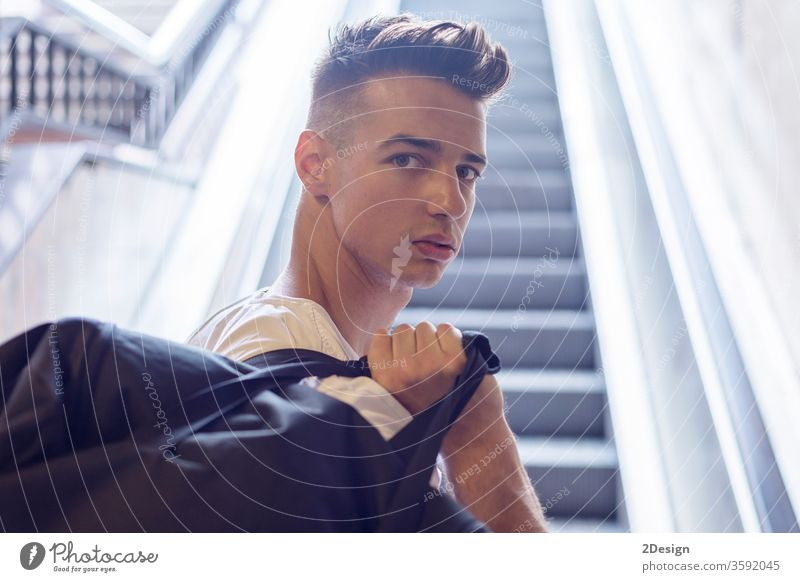 Hübscher junger Mann mit weißem T-Shirt, der eine Tasche auf der Schulter trägt und in die Kamera schaut 20s männlich Ausdruck Blick Jugendzeit Erwachsener