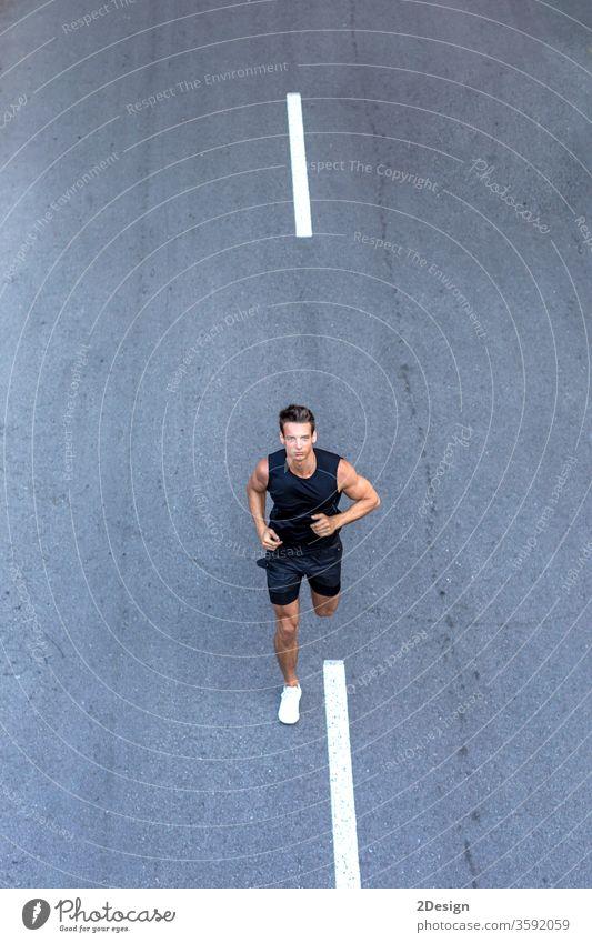 Draufsicht auf einen Athleten, der in schwarzer Sportkleidung auf der Straße trainiert. Mann Erwachsener Joggen Lifestyle sportlich Läufer Übung jung aktiv