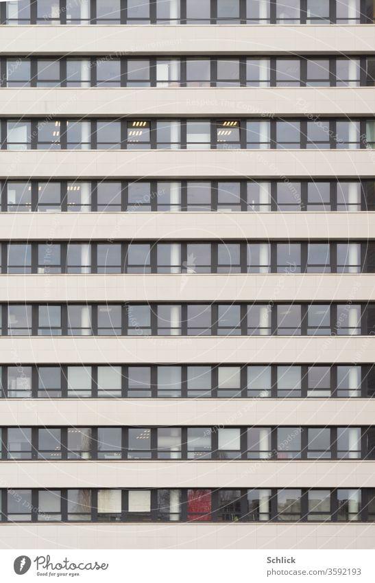 Fassade eines Bürogebäudes mit vielen Fenstern frontal Tag Neonlampen modern Quadrate Rechtecke Alufenster Stockwerke Hochhaus Beton ohne Himmel grau schwarz