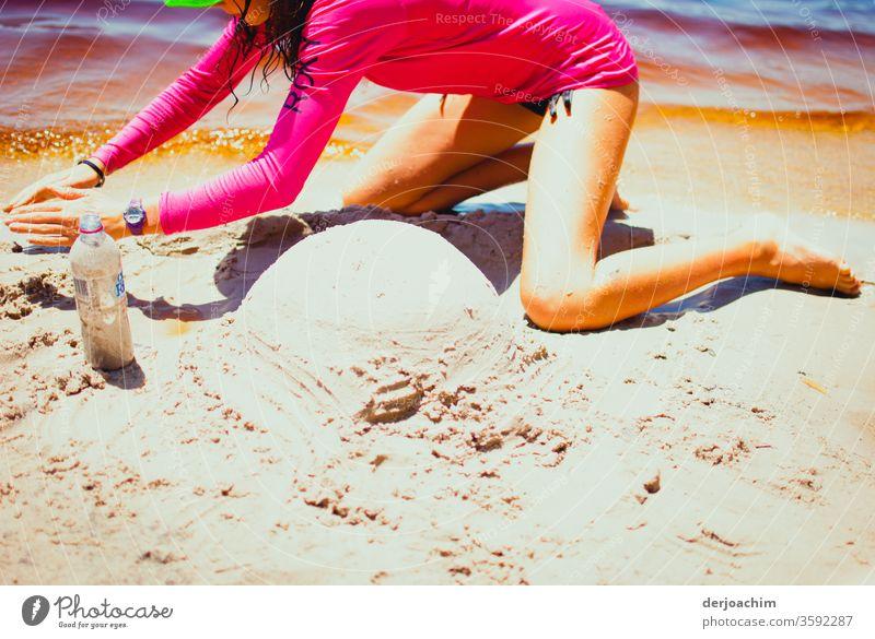 Im heißen Sand soll ein Australia Schneemann gebaut werden. Eim Mädchen im roten Badeanzug am Wasser hat schon einen kleinen runden Hügel geformt. Sommer Strand