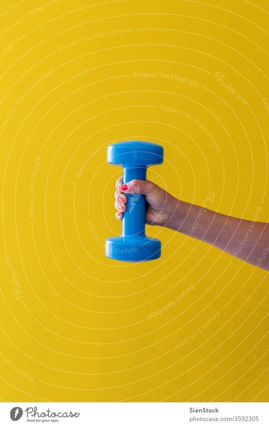 Die Hand der Frau hält eine Hantel auf gelbem Hintergrund Aktivität Stil greifen Beteiligung Nägel rot Lifestyle physisch Arme schwer Konzept vereinzelt