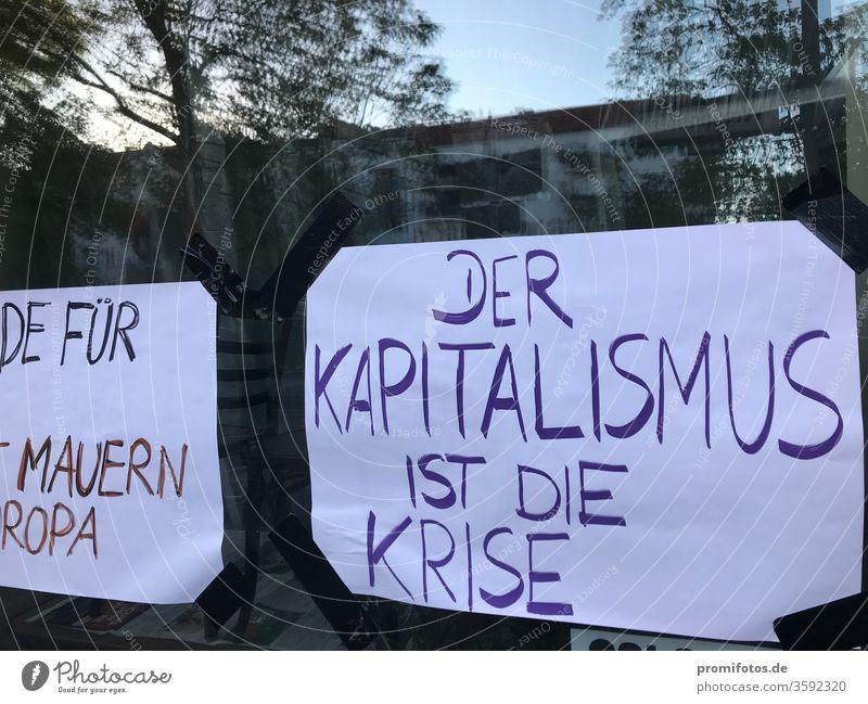 """Schaufensteraushang: """"Der Kapitalismus ist die Krise"""". Foto: Alexander Hauk Neoliberalismus Protest Demokratie Meinungsfreiheit Spiegelung Tageslicht"""