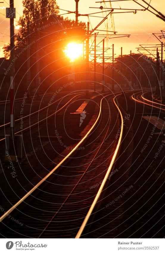 Sonnenuntergang verwandelt Schienenstrang in goldenen Pfad Abenddämmerung Licht Linie Melancholie Eisenbahnschiene Straße Geschwindigkeit Stahl Bahn Verkehr Zug