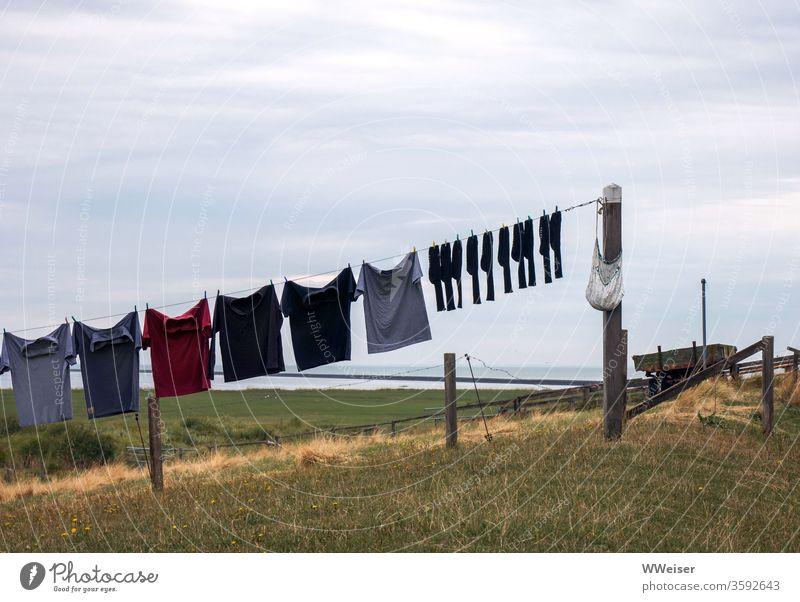 Wäscheleine bei bewölktem Wetter Wäscherei Hemden Socken diagonal trüb trocknen Kleiderhaken hängen Bekleidung Landleben paarweise Aus Wechsel hallig Nordsee