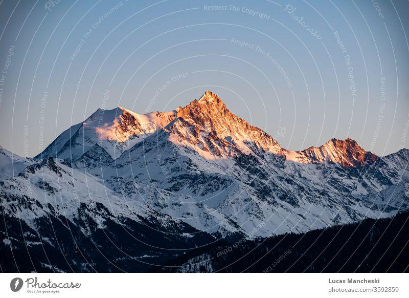 Schweizer Alpen zur goldenen Stunde des Sonnenuntergangs in den kalten Wintern von Crans Montana, Schweiz alpin Ehrfurcht atemberaubend Wolken feurig Einfrieren