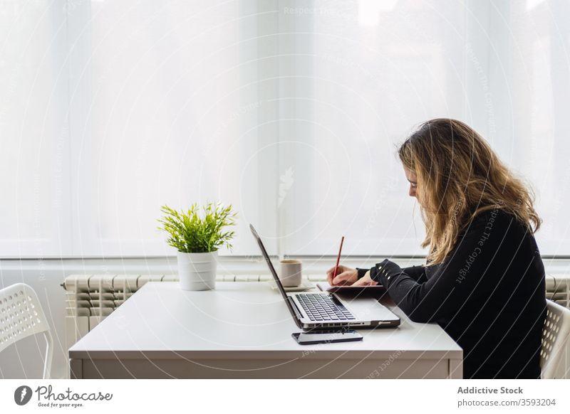 Junge Frau, die zu Hause mit dem Laptop arbeitet Arbeit heimwärts zur Kenntnis nehmen online abgelegen Tisch lässig beschäftigt jung Arbeitsplatz freiberuflich