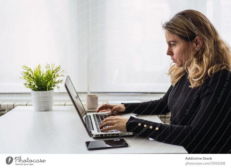Junge Frau, die zu Hause mit dem Laptop arbeitet Arbeit heimwärts online abgelegen Tisch lässig beschäftigt jung Arbeitsplatz freiberuflich Gerät Apparatur