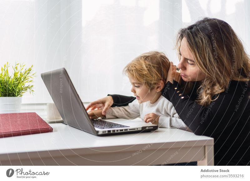 Frau mit kleinem Kind arbeitet zu Hause am Laptop Arbeit heimwärts Mutter benutzend Zusammensein online beschäftigt abgelegen neugierig Punkt Mutterschaft