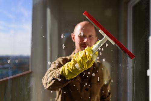 Mann wäscht Fenster in gelben Gummihandschuhen Raumpfleger Sauberkeit heimisch Arbeit Glas Rakel Hausarbeit Waschen Wasser Person Hygiene heimwärts durchsichtig