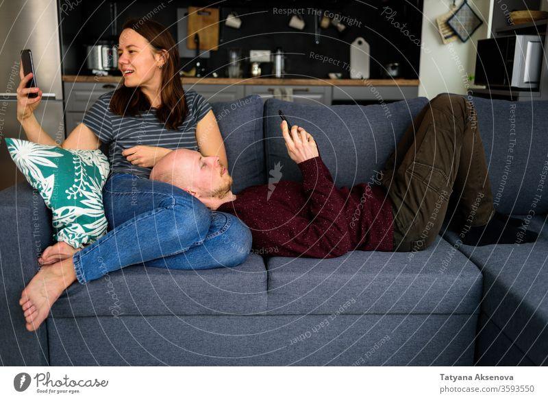 Telefonierendes Ehepaar sitzt in der Küche auf der Couch online Paar benutzend Sucht Internet Problematik Texten Surfen Bildschirm Ehemann Ehefrau Smartphone