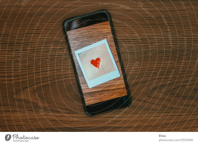 Ein Foto mit einem Herz auf dem Bildschirm eines Smartphones. Online Dating. Tinder. Kommunikation. Liebe Display Polaroid Symbol Gefühle Emotionen chatten