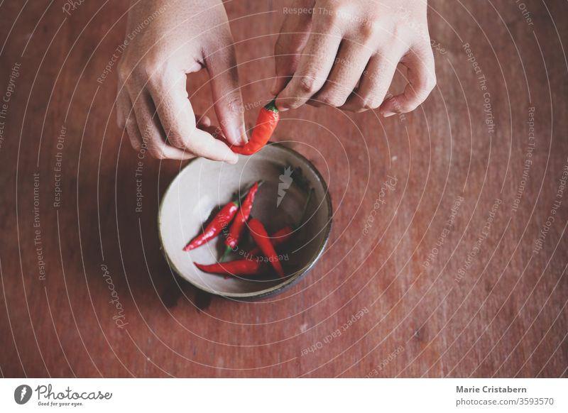 Nahaufnahme von Händen, die rote Chilis zum Kochen vorbereiten, um das Konzept der Gastronomie, der Küche, der sauberen und gesunden Ernährung und der ayurvedischen Küche zu zeigen