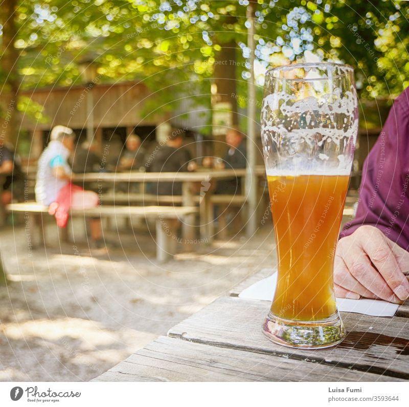 Glas bayrisches Bier im Biergarten, verschwommener Hintergrund typisch bayerisch trinken Bierschaum unter freiem Himmel saisonbedingt Restaurant