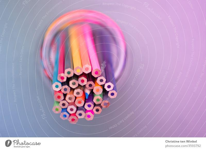 Kunterbunte leuchtende Buntstifte stehen mit den Spitzen nach unten (bis auf einen) schräg in einem Glas. Vogelperspektive. bunt gemischt Stifte zeichnen malen