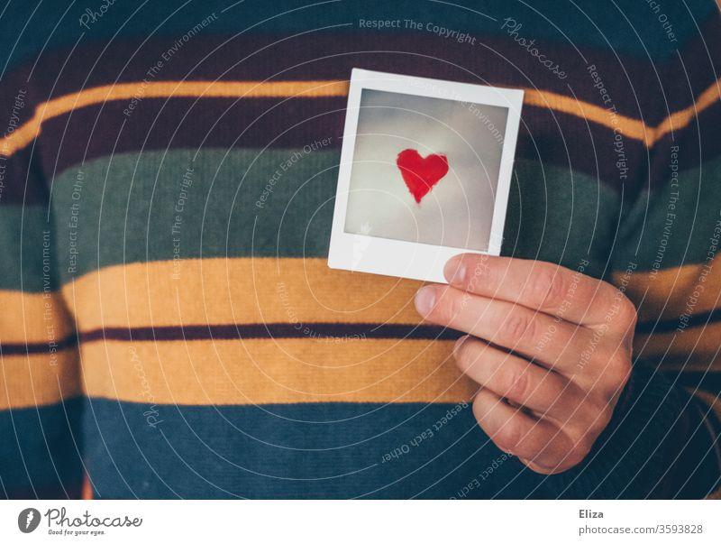Ein Mann zeigt Gefühle. Herz und Liebe. zeigen Verliebtheit Romantik rot Valentinstag Muttertag Emotionen flirten Sympathie Symbolik Pulli Brust Zusammensein