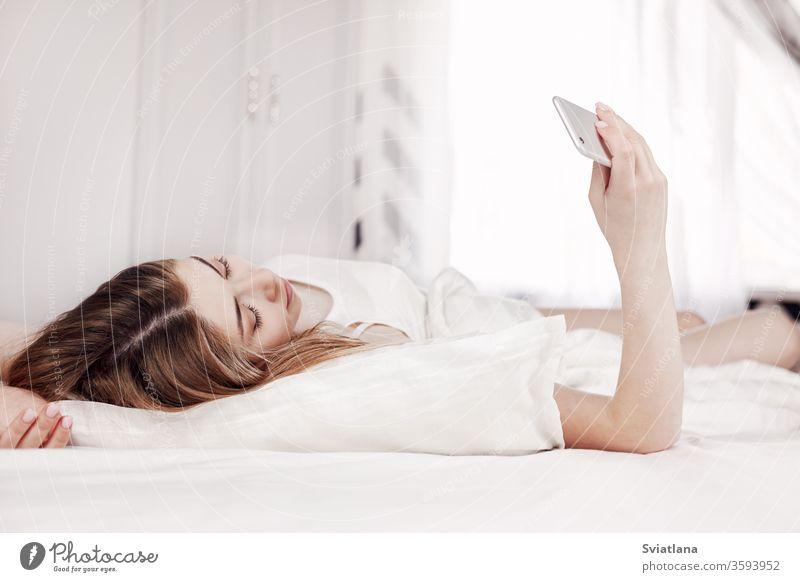 Ein hübsches junges Mädchen schaut auf das Telefon, während sie auf dem Bett liegt. Ein Mädchen liest Nachrichten auf ihrem Telefon, wenn sie morgens aufwacht