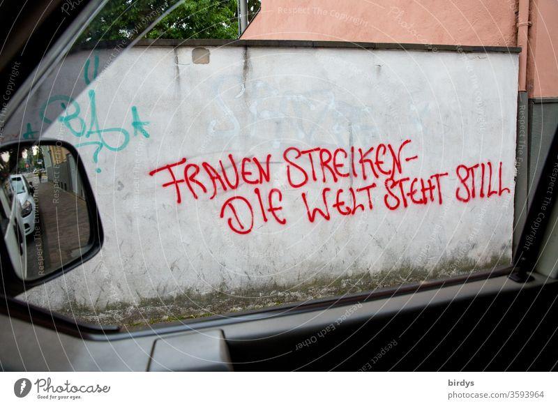"""Grafitti mit Text auf einer Mauer durch ein Seitenfenster eines Autos fotografiert."""" Frauen streiken- die Welt steht still."""" Gleichberechtigung, Hinweis auf die wichtige Rolle der Frau in der Welt und der Ruf nach Gleichstellung."""